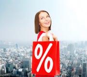 红色礼服的妇女有购物袋的 免版税图库摄影
