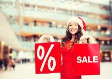 红色礼服的妇女有购物袋的 免版税库存图片