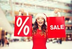 红色礼服的妇女有购物袋的 免版税库存照片
