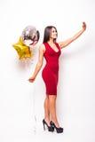 红色礼服的妇女有从电话的形状的气球作为selfie的 库存图片