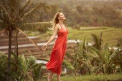 红色礼服的妇女 米大阳台 免版税库存照片