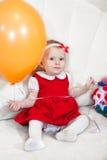红色礼服的小女婴与玩具坐白色长沙发 免版税库存图片
