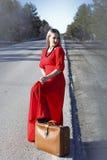 红色礼服的少妇在有红色行李的路 免版税库存照片