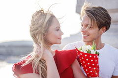 红色礼服的少妇在第一个日期得到花束 库存图片