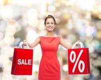 红色礼服的少妇有购物袋的 库存照片
