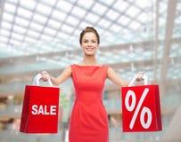 红色礼服的少妇有购物袋的 免版税库存图片