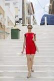 红色礼服的少妇,恭敬地举行白色,去楼下 免版税图库摄影