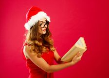 红色礼服的年轻可爱的圣诞老人女孩在红色背景 库存图片