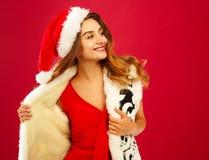 红色礼服的年轻可爱的圣诞老人女孩在红色背景 免版税库存图片