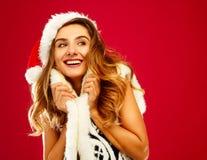 红色礼服的年轻可爱的圣诞老人女孩在红色背景 库存照片