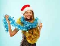 红色礼服的年轻可爱的圣诞老人女孩在蓝色背景 免版税图库摄影