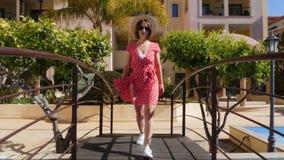 红色礼服的年轻可爱的妇女有太阳镜和帽子的走在游泳场的桥梁的在棕榈树旅馆ga里 股票视频