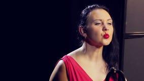 红色礼服的年轻女人有红色口红的微笑着 特写镜头 股票视频