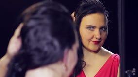 红色礼服的年轻女人有红色口红的调直她的在镜子和微笑前面的头发 股票录像
