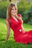 红色礼服的年轻美丽的微笑的妇女坐一个绿色草甸在城市公园 库存图片