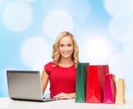 红色礼服的微笑的妇女有礼物和膝上型计算机的 免版税库存图片