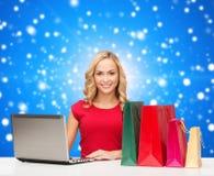 红色礼服的微笑的妇女有礼物和膝上型计算机的 库存照片