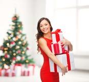 红色礼服的微笑的妇女有许多礼物盒的 免版税库存照片