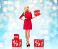 红色礼服的微笑的妇女有购物的签字 免版税库存照片