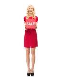 红色礼服的微笑的妇女有购物的签字 免版税库存图片