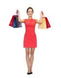 红色礼服的微笑的妇女有购物袋的 库存图片