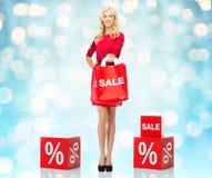 红色礼服的微笑的妇女有购物袋的 免版税库存照片