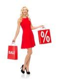 红色礼服的微笑的妇女有购物袋的 免版税图库摄影