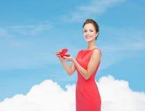 红色礼服的微笑的少妇有礼物盒的 免版税库存图片
