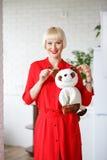 红色礼服的快乐的妇女有一个玩具狗的在站立的手上  图库摄影