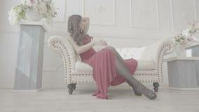 红色礼服的性感的热的女孩坐长沙发在豪华屋子里 股票视频