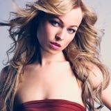 红色礼服的性感的白种人少妇有长的金发的 免版税库存照片