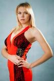 红色礼服的性感的白肤金发的妇女 库存照片