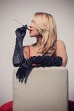 红色礼服的性感的金发碧眼的女人坐与香烟的椅子 库存照片