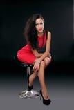 红色礼服的性感的年轻华美的深色的妇女在椅子,是 免版税库存图片