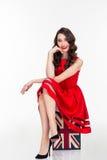 红色礼服的愉快的可爱的妇女坐葡萄酒手提箱 库存图片