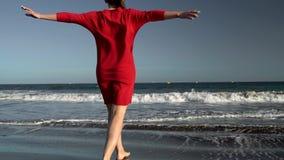 红色礼服的愉快的少妇走到在海洋海滩的水的在日落 无忧无虑的现代生活的概念 慢 影视素材