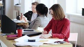 红色礼服的愉快的被聚焦的女商人非常繁忙与文书工作,写在文件在现代办公室桌上 影视素材