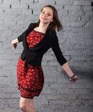 红色礼服的新逗人喜爱的深色的青少年的女孩 免版税库存图片