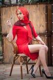 红色礼服的时兴的可爱的白肤金发的妇女坐椅子 有摆在典雅的场面的红色围巾的美丽的端庄的妇女 库存照片