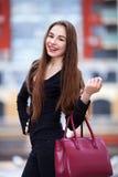红色礼服的时兴的女孩有穿过城市街道的袋子的 图库摄影