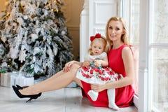 红色礼服的母亲微笑并且拿着一个可爱的女婴白肤金发的w 库存图片