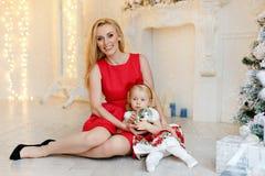红色礼服的母亲微笑并且拿着一个可爱的女婴白肤金发的w 免版税库存图片