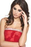 红色礼服的沉思美丽的妇女 免版税库存照片