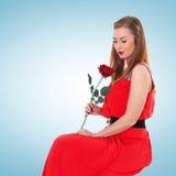 红色礼服的浪漫端庄的妇女有花的起来了 免版税库存照片