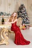 红色礼服的白肤金发的妇女有白葡萄酒或香槟选址玻璃的在一把椅子的在豪华内部 圣诞节我的投资组合结构树向量版本 库存照片