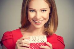 红色礼服的秀丽女孩有礼物盒的对生日或情人节 免版税库存照片