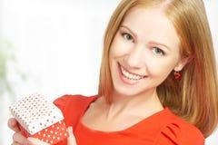红色礼服的秀丽女孩有礼物盒的对生日或情人节 免版税库存图片