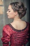 红色礼服的美丽的中世纪妇女 免版税库存照片