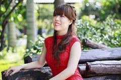 红色礼服的美丽的亚裔女孩 免版税库存照片