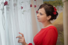 红色礼服的美丽的女孩在窗口看 图库摄影